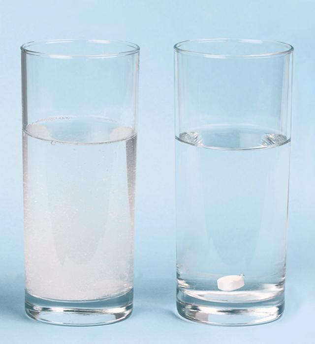 To glass med vann- et med en oppløst Bio-Magnesium-tablett og en med en annen magnesiumtablett som ikke viser tegn til å løses opp